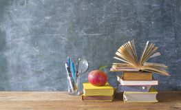 Back to school and education supplies. Books, pens, on black board background, good copy space Stock Image