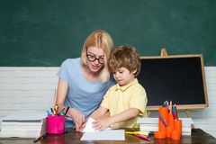 Back to school. Educational process. Great study achievement. Child and teacher near chalkboard in school classroom. royalty free stock images