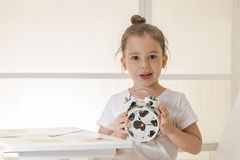 Back to school!. Expressive little girl holding alarm clock sitting at a desk indoor shot Royalty Free Stock Image