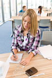 Back to school - female student in classroom. Writing notes Stock Photo
