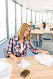 Back to school - female student in classroom. Writing notes Stock Images
