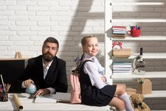 Back to school and first school day concept. Family sits by desk with school supplies. Schoolgirl and her dad with satisfied faces wearing bag. Girl and father royalty free stock photo