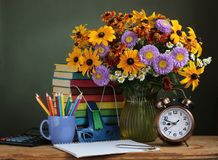Back to school. The first of September, Knowledge day, Teacher`s. Day. Still life with autumn bouquet, and school supplies royalty free stock image