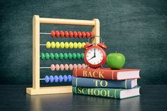 Back to school. Front view of a vintage alarm clock, an abacus with text: back to school and a stack of books, chalkboard on background with empty space (3d Royalty Free Stock Photography