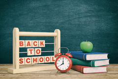 Back to school. Front view of a vintage alarm clock, an abacus with text: back to school and a stack of books, chalkboard on background with empty space 3d Royalty Free Stock Images