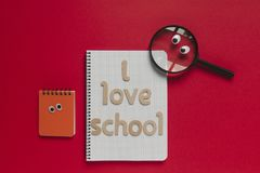 Cartoon school stuff and `I love school` lettering on a notebook. Red background. Back to school funny concept with wooden letters in red background Stock Photo