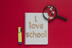 Magnifying glass with eyes looking at `I love school` lettering on a notebook. Red background. Back to school funny concept with wooden letters in red Royalty Free Stock Image