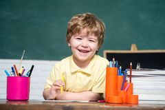 Back to school. Funny little kid pointing up on blackboard. Cute little preschool kid boy in a classroom. Back to school. Funny little kid pointing up on royalty free stock photography