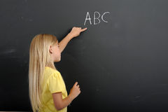 Back to school: girl writing ABC on a chalkboard Stock Image