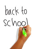 Back to school. Girls hand holding green pen writing back to school greeting card Stock Image