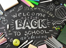 `Back to school` handwritten with school supplies on a black background. Top view Royalty Free Stock Photo
