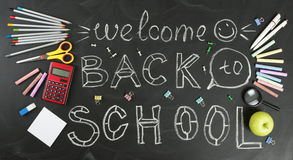 `Back to school` handwritten with school supplies on a black background. Top view Stock Photo