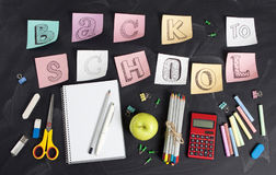 `Back to school` handwritten with school supplies on a black background. Top view. `Back to school` handwritten with school supplies on a black background. Top Royalty Free Stock Photo