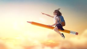 Child flying on a pencil. Back to school! Happy cute industrious child flying on the pencil on background of sunset sky. Concept of education and reading. The stock photography