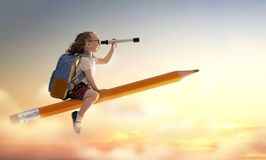 Child flying on a pencil. Back to school! Happy cute industrious child flying on the pencil on background of sunset sky. Concept of education and reading. The royalty free stock image