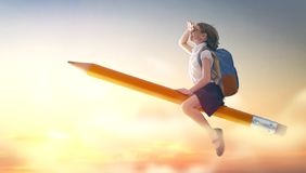 Child flying on a pencil. Back to school! Happy cute industrious child flying on the pencil on background of sunset sky. Concept of education and reading. The royalty free stock photo