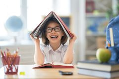 Kid is learning in class. Back to school! Happy cute industrious child is sitting at a desk indoors. Kid is learning in class royalty free stock photography