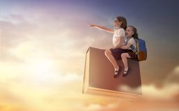 Children flying on the book. Back to school! Happy cute industrious children are flying on the book on background of sunset sky. Concept of education and reading royalty free stock image