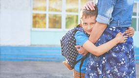 Back to school. Happy mother and son embrace in front of the elementary school royalty free stock photography