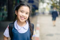 Back to school. Happy smiling girl from elementary school at the stock images