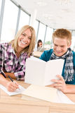 Back to school - happy students with books. In classroom Stock Image