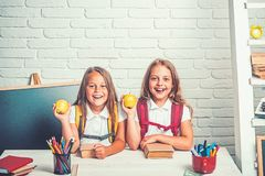 Back to school and home schooling. Friendship of small sisters in classroom at knowledge day. Little girls eat apple at. Lunch break. School time of girls stock image