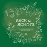 Back to school inscription on chalkboard with autumn leaves Royalty Free Stock Images