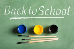 Back to school inscription on the chalkboard. Paintbrushes and paints on a green chalkboard (top view). Back to school concept Stock Images