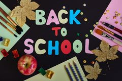 Back to school inscription made of colored letters, school supplies, ripe red apple and autumn leaves on the black background. stock photos