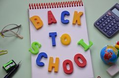 Back to school. Items for the school on a green table. inscription in colored letters back to school. notebook, notebook stock images