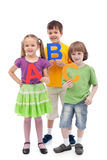 Back to school - kids holding large abc letters. Isolated stock image