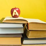 Back to school and knowledge concept. Stack of books and fresh red apple with mark A on wooden background and trendy yellow wall stock photos