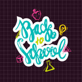 Back to School lettering hand drawn design. Colorful Label isolated on dark background with apple, book, pencil. Stock Photo