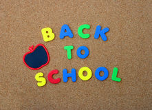 Back To School letters with Chalkboard Apple. Colorful Back To School letters with Chalkboard Apple on Cork Board Royalty Free Stock Photo