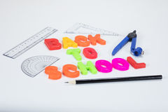 Back to school letters and geometry accessories. Back to school written with colourful alphabet learning letters alongside a pencil, protractor, ruler and Royalty Free Stock Photography