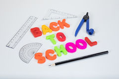 Back to school letters and geometry equipment. Back to school written with colourful alphabet learning letters alongside a pencil, protractor, ruler and geometry Royalty Free Stock Image