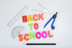 Back to school letters and geometry supplies. Back to school written with colourful alphabet learning letters alongside a pencil, protractor, ruler and geometry Royalty Free Stock Image