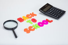 Back to school letters with learning equipment. Back to school written in alphabet learning letters alongside a calculator and magnifying glass with white copy Royalty Free Stock Photos