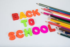 Back to school letters and multicoloured pencils. Back to school written with colourful alphabet learning letters beside coloured children pencils on a plain Royalty Free Stock Images