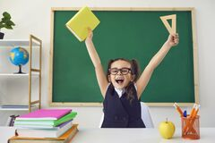 Free Back To School. Little Happy Schoolchild Raised Hands Up Against The Background Of A Green Blackboard In A Classroom. Stock Photo - 189252810
