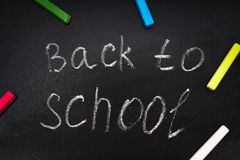 Back to school message on Blackboard inscribed with colorful chalk for background. Stock Photo