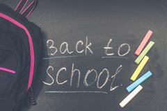 Back to school message on Blackboard inscribed with colorful chalk for background. Backpack. Back to school message on Blackboard inscribed with colorful chalk Stock Photos