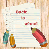 Back to school message with pencils on paper sheet. wooden backg Stock Photos