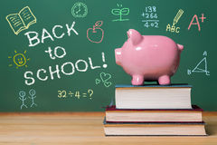 Back to School message with pink piggy bank on top of books Stock Photo