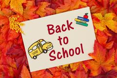 Back to School message. Some fall leaves with a blank beige greeting card with a school bus and books with text Back to School royalty free stock photography