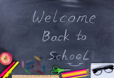 Back to school message with student supplies on chalkboard Stock Images