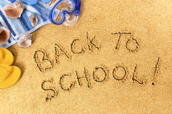 Back to school message written on beach sand, end of summer vacation concept Stock Photo