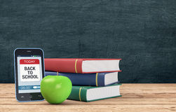Back to school. Mobile phone with a reminder app, a stack of books and a green apple, chalkboard with empty space on background, concept of back to school (3d Royalty Free Stock Photography