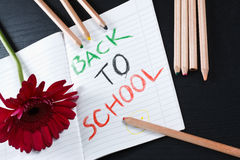 Back to school notice with flower and pencils. An exercise book with a coloured notice 'back to school' on it, a red daisy and some coloured pencils on a black Royalty Free Stock Images