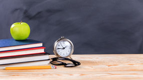 Back to school objects in front of erased black chalkboard. Back to school concept with green apple, pencils, clock, glasses and books in front of erased black royalty free stock photography